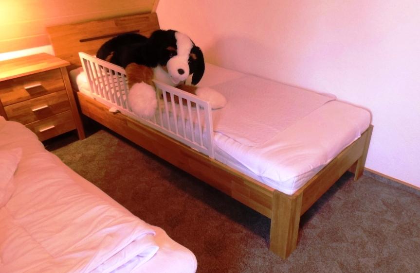 Bett mit Rausfallschutz im kleinen Schlafzimmer